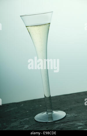 champagne, sparkling wine flute in a stylish tall fluted glass served on an old wooden bar counter, tilted angle - Stock Photo