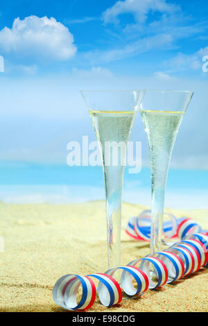 champagne flutes in elegant fluted glasses and a colourful red, white and blue twirled party streamer standing on - Stock Photo