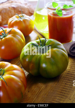 Unripe green ribbed tomato on a kitchen table with other ripe red tomatoes for use in preparing fresh tomato paste - Stock Photo