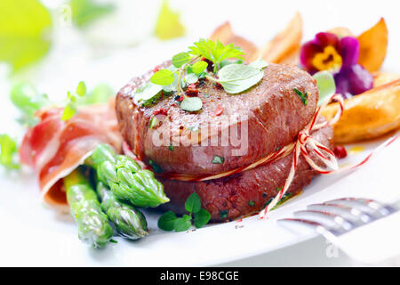 Thick juicy steak with fresh green asparagus spears wrapped in thinly sliced ham or bacon served garnished with - Stock Photo
