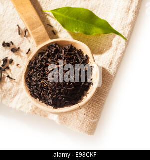 Close up overhead view of a small rustic wooden spoon filled with loose dried shredded tea leaves for making a refreshing - Stock Photo
