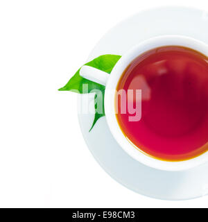 Overhead view of a refreshing cup of freshly brewed black tea with two green tea leaves in the saucer isolated on - Stock Photo