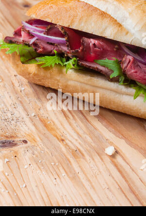Fresh baguette with a filling of sliced roast beef, lettuce, tomato, onion and herbs on a wooden table top with - Stock Photo
