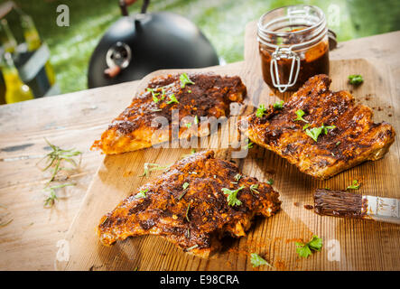 Basting and seasoning ribs for the BBQ with three portions of meat laid out on a wooden picnic table in a summer - Stock Photo