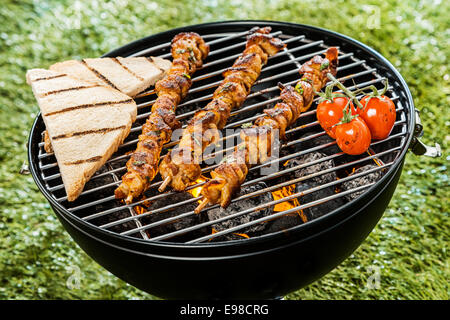 Three delicious meat kebabs grilling on a BBQ fire with slices of toast and tomatoes during a summer picnic in the - Stock Photo
