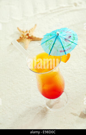 Tropical Cocktail With Paper Umbrella On The Sand