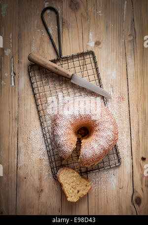 Overhead view of a slice cut from a freshly baked ring cake cooling on a wire rack in a country kitchen on an old - Stock Photo