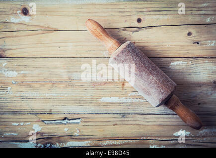 Old wooden rolling pin on a grunge wood background with remnants of scattered flour left over from baking overhead - Stock Photo