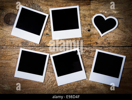 Six empty instant photo frames lying on rustic rough weathered wooden boards, with one heart-shaped for a nostalgic - Stock Photo