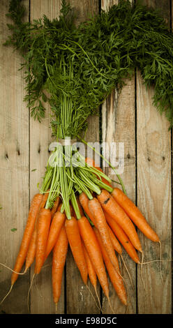Overhead view of a bunch of fresh organic carrots at market with their green leaves still attached lying on a rustic - Stock Photo