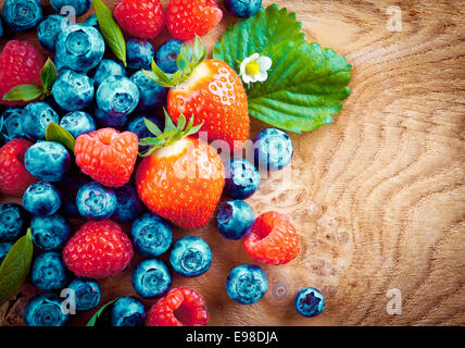 Overhead view of mixed ripe autumn berries including strawberries, raspberries and blueberries on a decorative woodgrain - Stock Photo