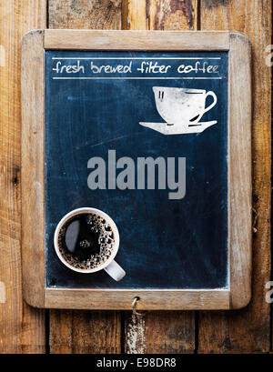 Fresh brewed filter coffee - handwritten on an old vintage school slate used as an advertising sign in a rustic - Stock Photo
