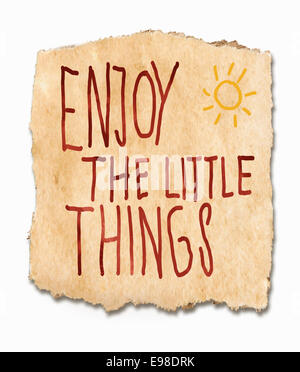 Enjoy the lttle things, an inspirational saying handwritten on a torn fragment of textured, grunge, paper with a - Stock Photo