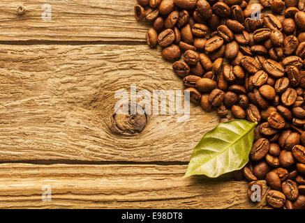Pile of fresh roasted coffee beans arranged as a corner border on textured rustic wood boards with a green coffee - Stock Photo