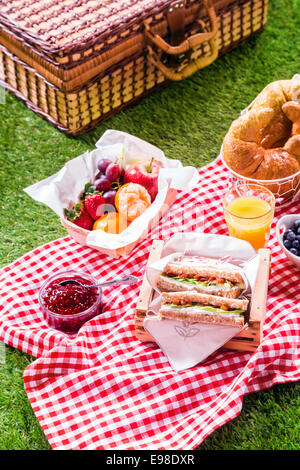 Healthy outdoor summer picnic with sandwiches, fresh fruit , croissants and orange juice laid out on a rustic red - Stock Photo