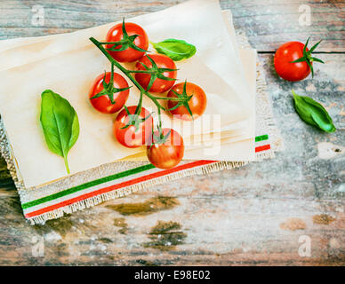 Cherry tomatoes, basil and dried lasagne sheets on an old weathered wooden table in a rustic kitchen ready to be - Stock Photo