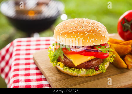 Tasty cheeseburger with melted cheddar cheese dripping over ground beef burger garnished with fresh salad ingredients - Stock Photo