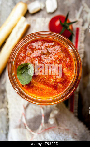 Spicy tomato dip with Italian grissini or crisp bread sticks for a delicious savory appetizer or snack - Stock Photo