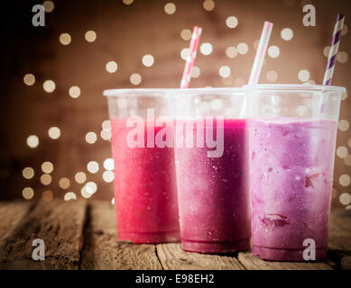 Three different colorful berry smoothies with twinkling party lights standing in a row on a rustic wooden counter - Stock Photo