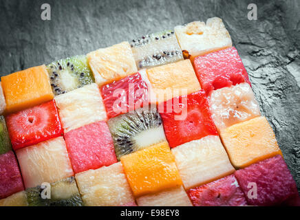 Cubed tropical fruit arranged in a decorative colorful square with a close up view showing the texture and pattern - Stock Photo