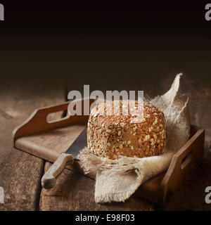 Delicious country whole grain bread for a healthy snack or accompaniment to a meal served on an old rustic wooden - Stock Photo