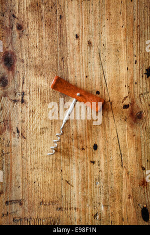 Manual corkscrew with a wooden handle and steel screw for opening bottles of wine lying centred on a textured wooden - Stock Photo