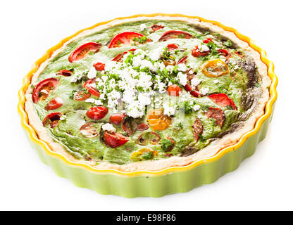 Savory egg, herb, tomato and cheese vegetarian quiche in a pastry crust served in a fluted pie dish on a white background - Stock Photo