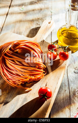 Ingredients for a tasty Italian tomato pasta dish with flavored linguine pasta. cherry tomatoes and olive oil on - Stock Photo