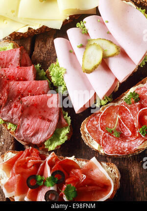 Array of tasty assorted open sandwiches on wholewheat and rye bread topped with gouda cheese, mortadella, roast - Stock Photo
