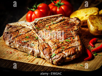 Grilled T-bone steak seasoned with spices and fresh herbs served on a wooden board with fresh tomato , roast potatoes - Stock Photo