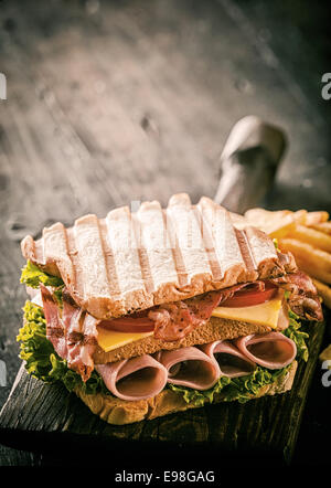 Healthy grilled ham, cheese and salad sandwich in double-decker form on toasted white bread served on an old wooden - Stock Photo