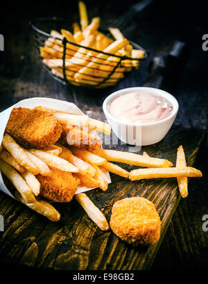 Crispy golden deep fried fish and potato chips, or French fries, served with a savory mayonnaise dip on an old wooden - Stock Photo