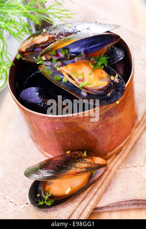 Delicious freshly boiled marine mussels in a copper saucepan with their shells open garnished with dill for a gourmet - Stock Photo