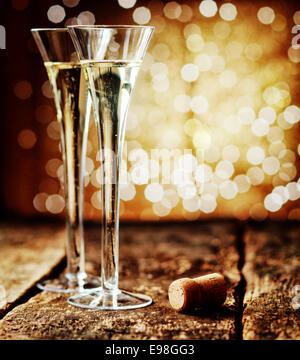 Two tall elegant flutes of romantic champagne on an old rustic wooden counter top against a sparkling bokeh of party - Stock Photo