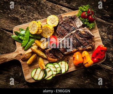 Delicious steakhouse porterhouse steak and colorful fresh roast vegetables with mangetout peas, corn, zucchini, - Stock Photo