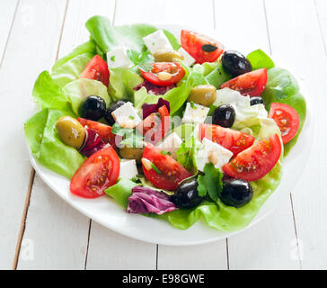 Fresh Mediterranean salad with feta cheese, olives, lettuce, fresh herbs and tomato drizzled with olive oil for - Stock Photo