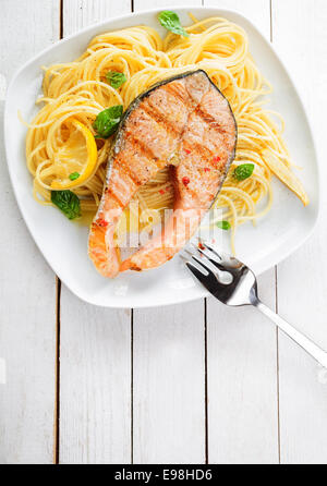 Gourmet seafood cuisine with grilled salmon cutlet steak served on a bed of Italian linguine pasta garnished with - Stock Photo