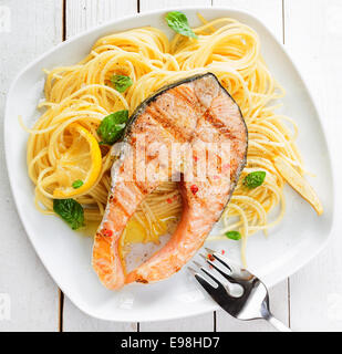 Healthy grilled salmon steak rich in omega-3 fatty acids served on linguine pasta topped with fresh basil , overhead - Stock Photo