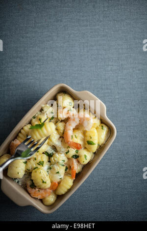 Overhead view of a dish of Italian gnocchi pasta, or semolina dumplings, with shrimps and fresh herbs with one pasta - Stock Photo