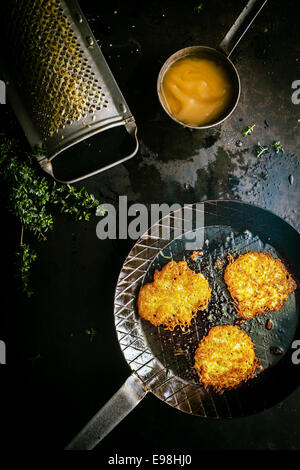 Delicious fresh fried potato fritters made from grated potato, fresh herbs and egg in a country kitchen with a vintage - Stock Photo