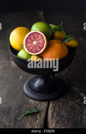 Pedestal bowl of assorted fresh citrus fruit with a halved blood orange displayed at the front on a rustic wooden - Stock Photo