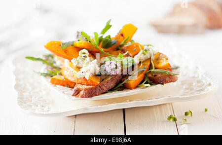 Gourmet Pumpkin Salad with Roasted Hokkaido and Grilled Bread. Served on White Wooden Table. - Stock Photo