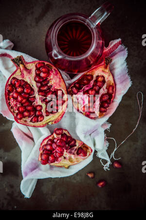 Making fresh pomegranate juice with an overhead view of a broken open fruit displaying the ripe red seeds on a stained - Stock Photo