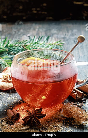Hot cup of spiced hot tea or gluhwein with a crystallized sugar stirrer and citrus fruit surrounded by dried cinammon - Stock Photo