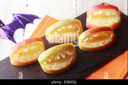 Scary Halloween apples with cutout teeth in an open mouth for a healthy fun favor for young kids trick-or-treating - Stock Photo