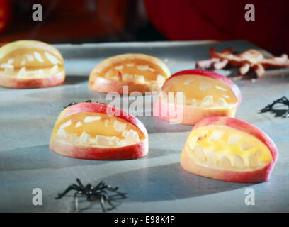 Scary Halloween decorations for trick-or-treat favors or party table decorations with gaping open apple mouths with - Stock Photo