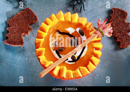 Halloween Pumpkin Soup Served in Half a Pumpkin with Bat Shaped Crouton Toasts and Broomstick Bread Stick from Above - Stock Photo