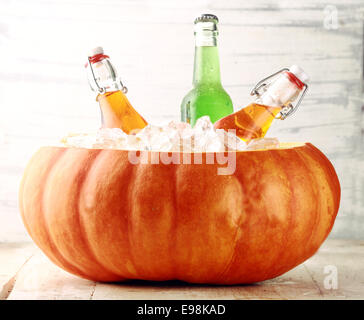 Bottled Alcoholic Beverages Chilling in Pumpkin Ice Bucket - Stock Photo