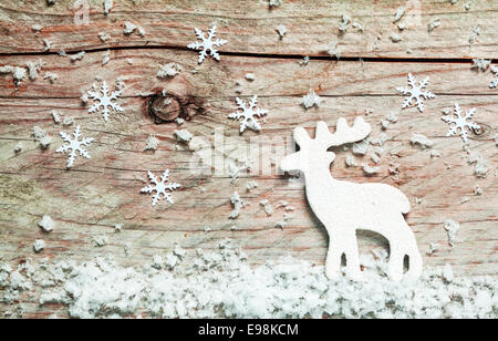 Christmas background with a reindeer in snow with falling decorative snowflakes on an old rustic wooden board - Stock Photo