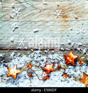 Golden stars with snow and falling snowflake decorations in a rustic Xmas background with copyspace for your Christmas - Stock Photo